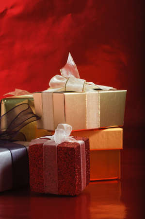 A selection of gift packages, tied with ribbons, against a foil red background.  Vertical (portrait) orientation. Stock Photo - 9948020