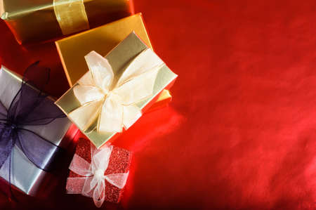 An overhead, horizontal shot of Christmas gift boxes, wrapped and tied with ribbon bows.  Copy space provided to the right on a reflective red background.  Imagens