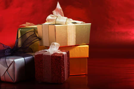 A selection of Christmas gifts, wrapped with tied ribbons against a metallic red background.  Copy space to right.  Horizontal (landscape) orientation.