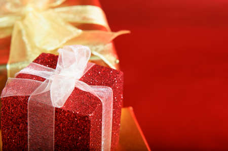 Close up of a glittery red gift box with white ribbon.  Gold box and bow in the background.  Red copy space to right.