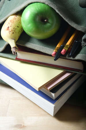 An open school satchel, containing books, pens, pencils and fruit.  Vertical (portrait) orientation.