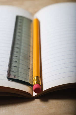 An opened students exercise book on a wooden table, blank pages revealed.  A pencil and ruler lie vertically in the centre seam.  Vertical (portrait) orientation. photo