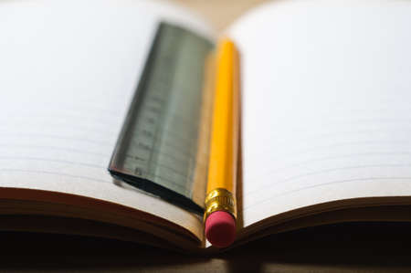 An opened students exercise book on a wooden table, blank pages revealed.  A pencil and ruler lie vertically in the centre seam. Horizontal (landscape) orientation. photo