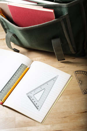 home schooling: A school satchel on a wooden table, behind an open exercise book with maths equipment.