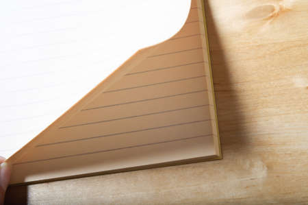 turning table: A fresh, blank page of a lined exercise book being turned to illustrate turning a new leaf.  Wooden table underneath.  Horizontal (landscape) orientation.