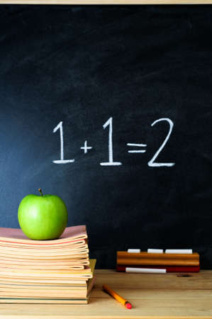 A school chalkboard and teachers desk with stack of exercise books and an apple.  The sum 1 + 1 = 2 is written on the chalkboard. Stock Photo