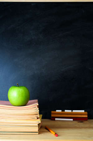 A school chalkboard and teachers desk with stack of exercise books and an apple. Copy space on blackboard.  Portrait (vertical) orientation.