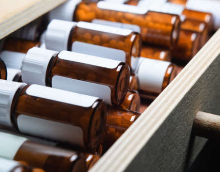 An open drawer, filled with many amber glass pill bottles containing homeopathic remedies
