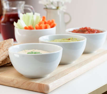 guacamole: A variety of dips, with pitta bread, crudites and juice on a table.