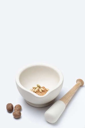 stoneware: A stoneware pestle and mortar with nutmeg, cardamon and mustard seeds.