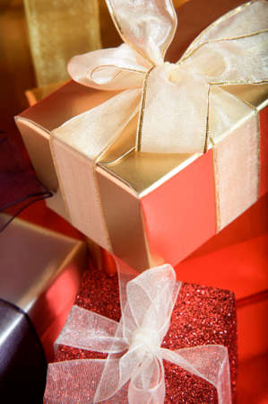 A pile of Christmas gifts, in shiny and sparkly packaging, tied in ribbosns with bows on a red reflective surface.   Stock Photo