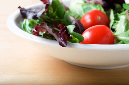 A white bowl of salad lettuces and tomatoes, including red lettuce and rocket, on a light wooden table. Stock Photo - 9948055