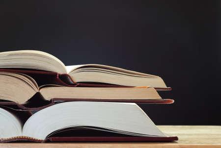 コピー領域のバック グラウンドで黒板 (黒板) と光の木製の机、3 つの開いた本の杭。横 (水平) 方向。