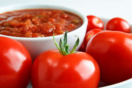 Close up (macro) of bright red tomatoes, surrounding a bowl of salsa in soft focus in the background.  Horizontal (landscape) orientation.