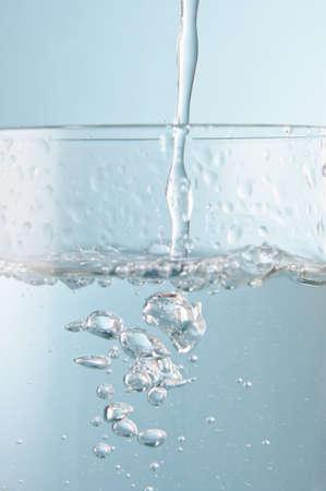 Photo d'action verticale de l'eau qui coule dans un verre sur un fond bleu glacé. Gros plan (macro). Banque d'images