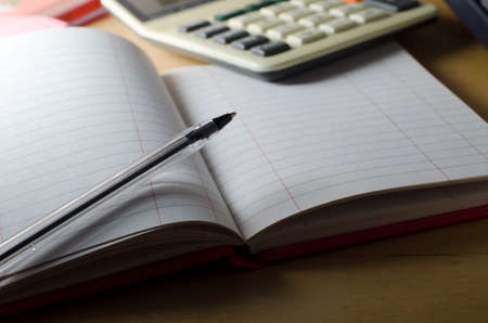 cash desk: A blank, ruled, two-column cash book lying open on a wooden desk with pen resting on page.  Calculator in soft focus background.