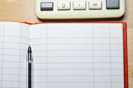 電卓、ペンで、木製の机の上の 2 つの列現金帳を開く。コピー スペースは空レジェ (元帳) 回線を介して提供されます。水平 (横) 方向。