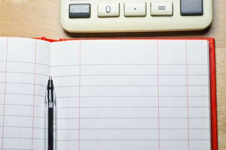 Une calculatrice et un dialogue ouvert, livre de deux espèces colonne avec stylo sur un bureau en bois. L'espace de copie est fournie via vides Leger (livre) lignes. Horizontal (paysage) d'orientation.
