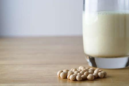 soja: Secos de soja (soya) de frijoles con un vaso de leche de soja en el fondo de enfoque suave sobre una mesa de madera clara. Horizontal (paisaje) la orientación.