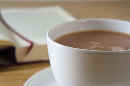 Close up (macro) of a cup of tea with saucer on a wooden table, with an open bookmarked novel in soft focus background.   photo