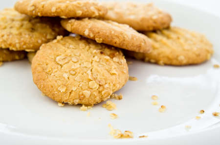 crumbly: A white plate of freshly baked crumbly oat biscuits (cookies), with crumbs.