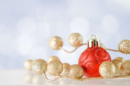 A red bauble with gold glitter balls on an icy reflective surface, with blue and white snow-effect bokeh background. photo