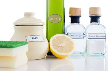 Eine Reihe von natürlichen, nicht-toxische Reinigungsmittel in Containern auf einem glänzenden reflektierende Oberfläche mit einem weißen Hintergrund.