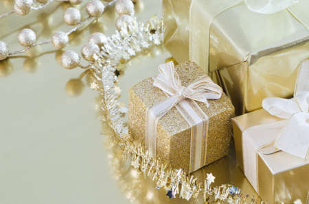 A collection of wrapped and tied Christmas gifts and decorations in gold shiny paper on reflective surface. photo