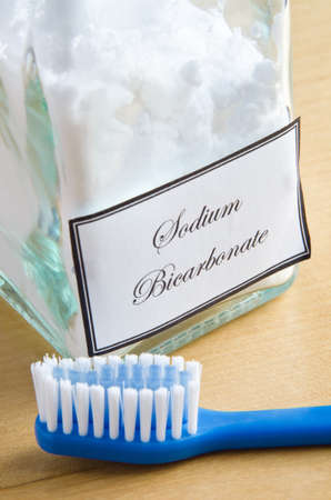 A bottle of sodium bicarbonate (baking soda) and a toothbrush on a wooden surface, to illustrate non-toxic dental care or natural toiletries. Imagens