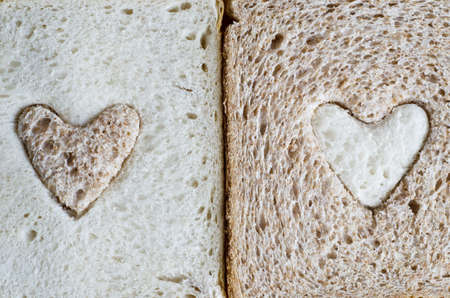 Close up of a white bread slice with a brown wholemeal heart, and a wholemeal bread slice with a white  heart.