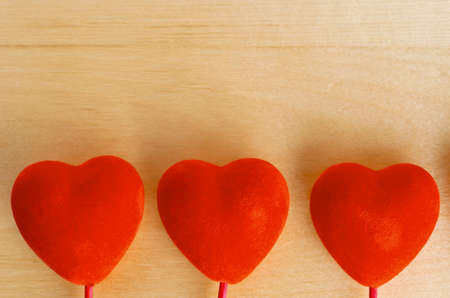 Three velvet-textured red hearts in a row at bottom of frame, with light grained wood background providing copy space above. photo