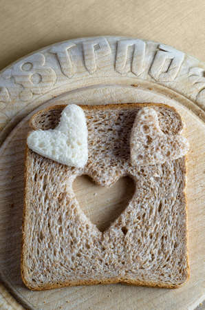 Overhead shot of white and brown wholemeal bread hearts and slice on an old, scratched vintage bread board with the word 'bread' embossed in the wood.   Stock Photo - 12245659