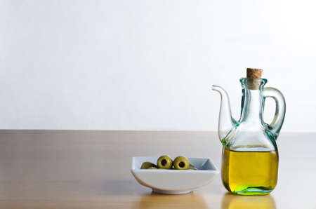 corked: A corked glass jug of olive oil, next to a bowl of olives on a wooden surface.  Off-white background and table provide copy space to left and above.