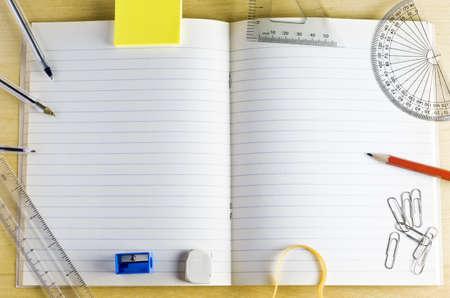 開かれた学校練習帳のオーバー ヘッド ショット。軽い木製の机の文房具に囲まれています。罫線付きのページは、コピー領域を提供します。