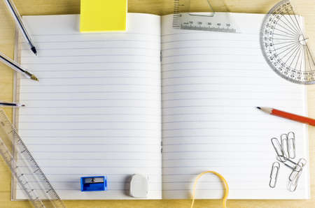 Vue aérienne d'un cahier d'école ouverte. entouré par les articles de papeterie sur un bureau en bois clair. Pages lignées fournissent l'espace de copie. Banque d'images