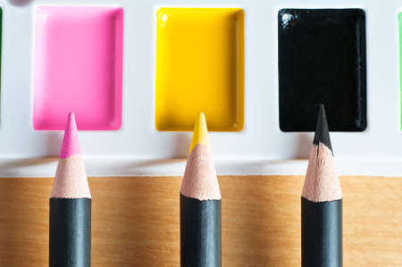 deciding: Close up of pencil tips pointing upwards to matching colours on a paint palette to illustrate colour matching or picking or mixed media. Stock Photo