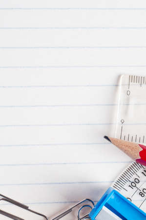 A selection of stationery bordering the bottom and right side of a lined paper background from a school exercise book. Stock Photo - 13052500