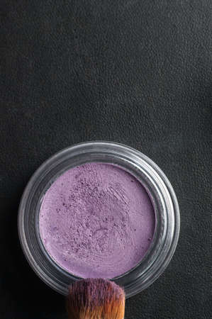 Overhead close up (macro) of an opened pot of purple eye shadow, with make up brush coated in powder on black leatherette background. photo