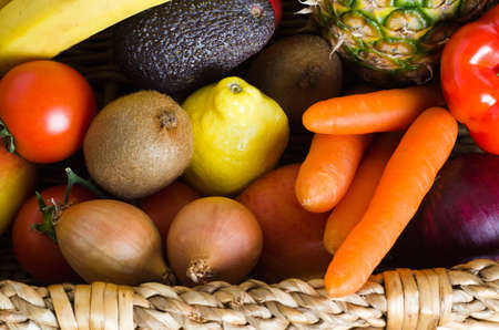 fruit and vegetables: Overhead shot of a basket crammed with raw, fresh, colourful fruit and vegetables.  Landscape orientation.