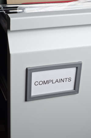 An opened filing cabinet drawer labeled Complaints, exposing hanging files and documents within.  Portrait orientation. photo