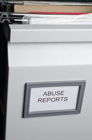 An open filing drawer containing hanging files and documents, labeled Abuse Reports.  Portrait orientation. photo