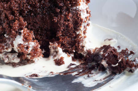 Close up (macro) of a partly eaten dessert of chocolate cake and double cream.  A fork in the foreground rests in the cream, with remnants of cake still on it. photo