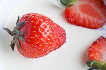 sunk: Close up (macro) of fresh strawberries sunk into rich double cream.   Stock Photo