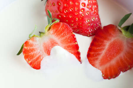 partly: Close up (macro) of whole and halved fresh strawberries with leaves, partly immersed in double cream.   Stock Photo