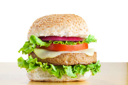A veggie burger (made from soya protein) in a sesame seed bap with layers of curly lettuce, melted cheese, tomato and onion, on a light wood table with white background.