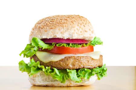 verduras: Una hamburguesa vegetariana (a base de proteína de soja) en una semilla de sésamo bautismo con capas de escarola, queso fundido, tomate y cebolla, en una mesa de madera clara con fondo blanco.