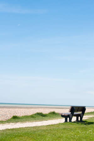 two and two thirds: A solitary, empty bench facing the sea on a path between grass and a shingle beach.  A softly clouded blue sky provides two thirds of copy space. Stock Photo