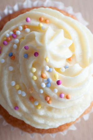 buttercream: Close up (macro) of a cupcake decorated with buttercream icing and colourful sprinkles, shot from above.