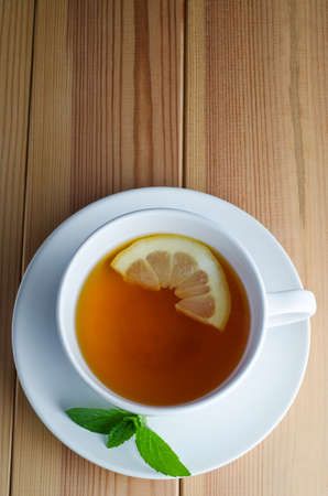 Overhead shot of lemon tea in a white cup and saucer with half a lemon slice and mint leaves on a wooden planked table