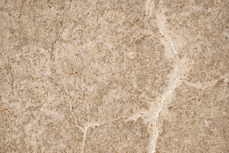 Background texture   Light beige coloured old stone wall with cracks and small pieces of grit on surface  photo